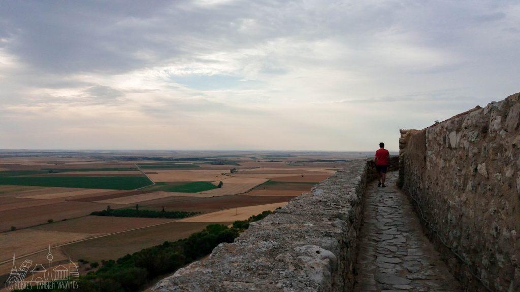 Paseo por las murallas de Urueña. A la izquierda los campos de Valladolid vistos desde lo alto, tonos verdes y ocres en forma de polígonos. A la derecha, y sobre la muralla, Juanjo caminando.