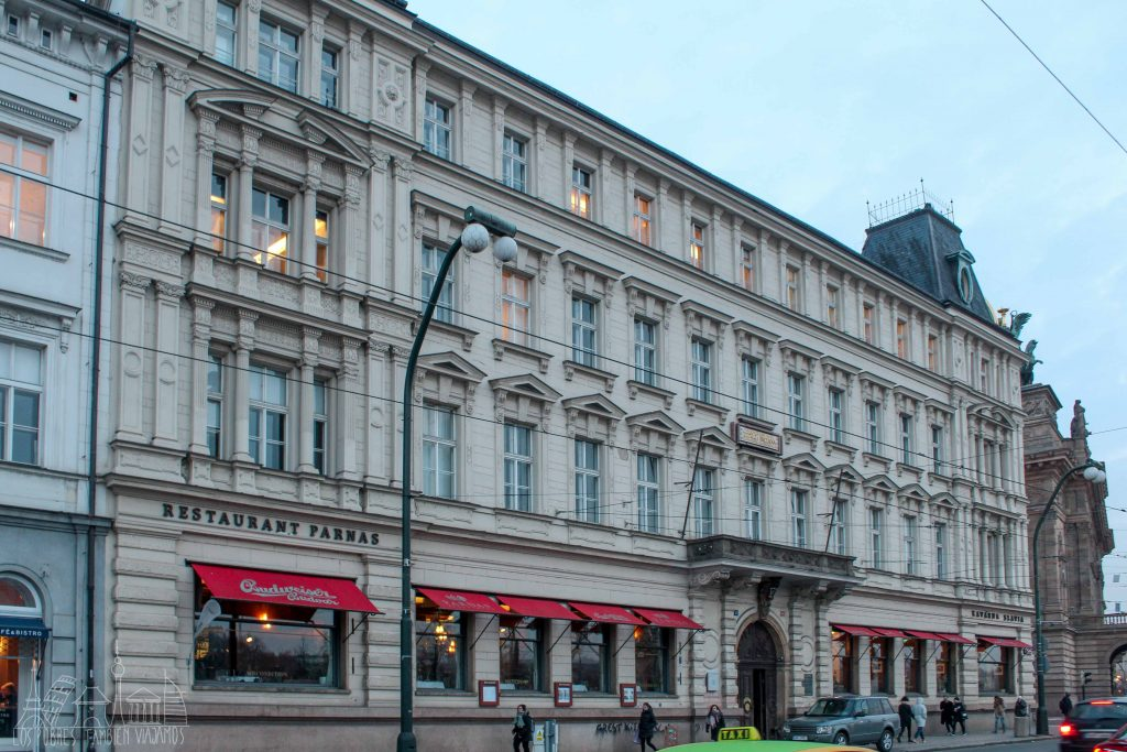 Gran edifico de 4 plantas de formas limpias, con ventanales en cada uno de los pisos. Parte inferior perteneciente a un restaurante. Toldos de color rojo dando a la calle.