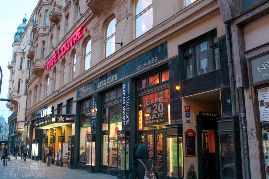 Marina caminando hacia el Café Louvre. Edificio con el rótulo en grandes letras rojas en el primer piso. En la planta baja la entrada al café y a su derecha un club de jazz.