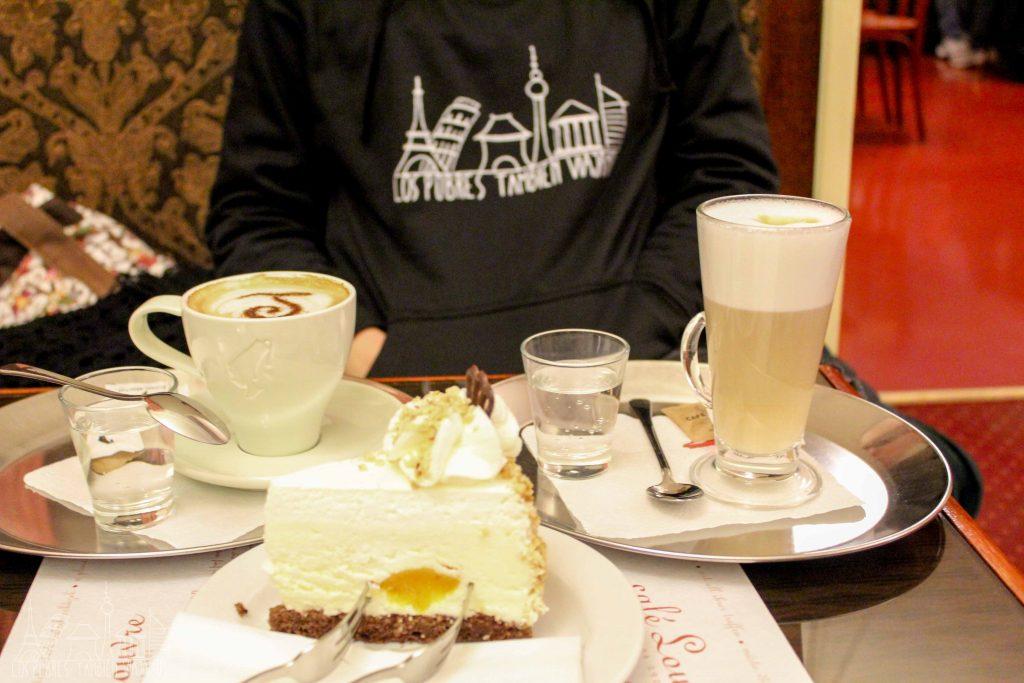 en primer plano una gran porción de tarta de queso. A la derecha un gran vaso de café latte y a la izquierda una gran taza de cappuccino. En segundo plano el tronco de marina con sudadera negra.