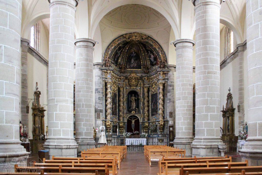 Interior de la iglesia de San Juan. Retablo barroco alf ondo en tonos oscuros y dorados. Grandes columnas muy robustas a los lados, bancos de manera en las dos secciones centrales y techos blancos abovedados.