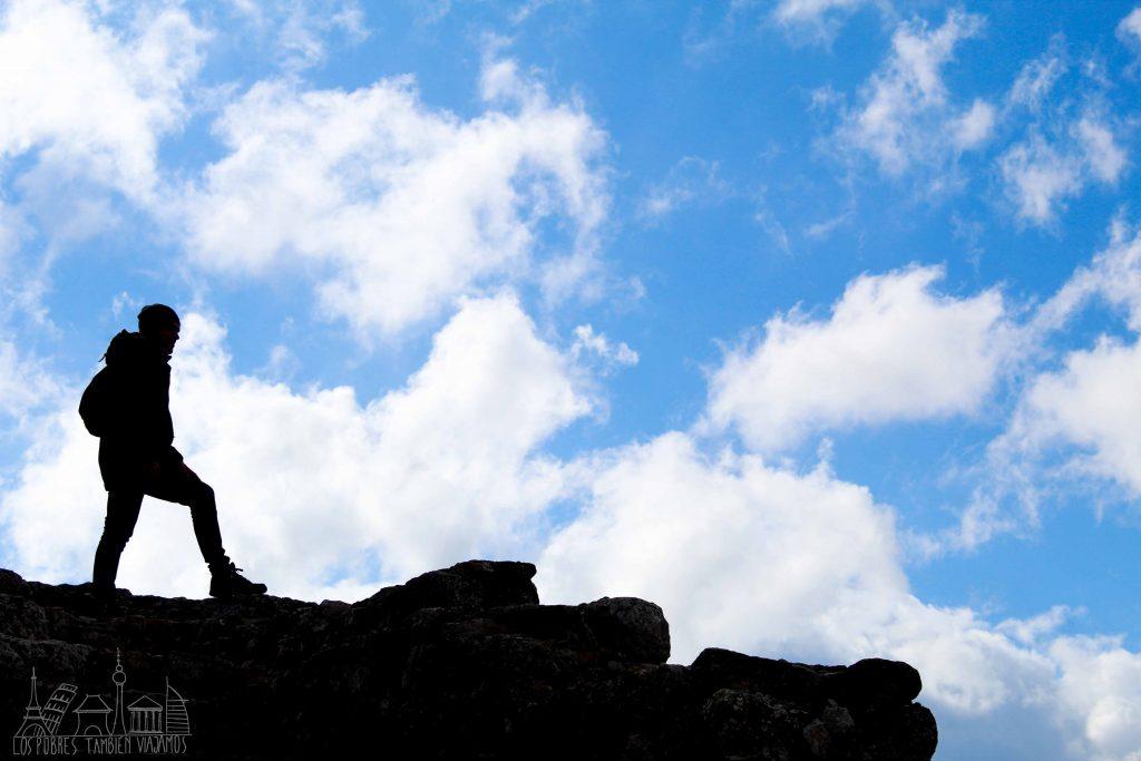 Juanjo sobre la muralla del castillo mirando al infinito. Un intenso cielo azul pintado de nubes blancas despunta en el fondo.