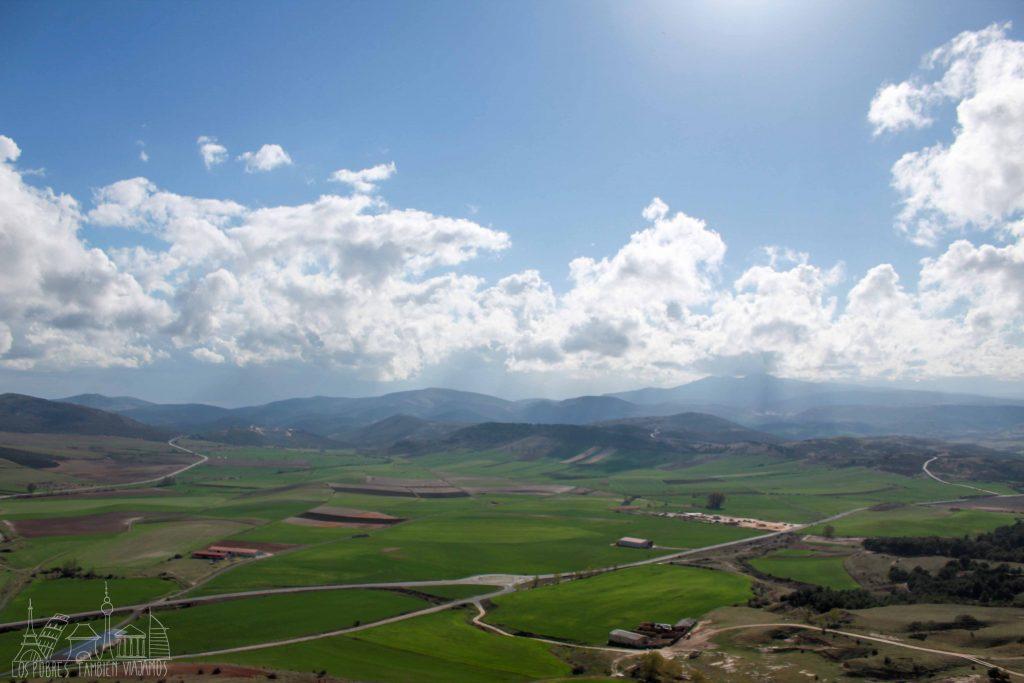 cielo azul, nubes bajaas, montañas al fondo y una gran extensión de prados verdes.