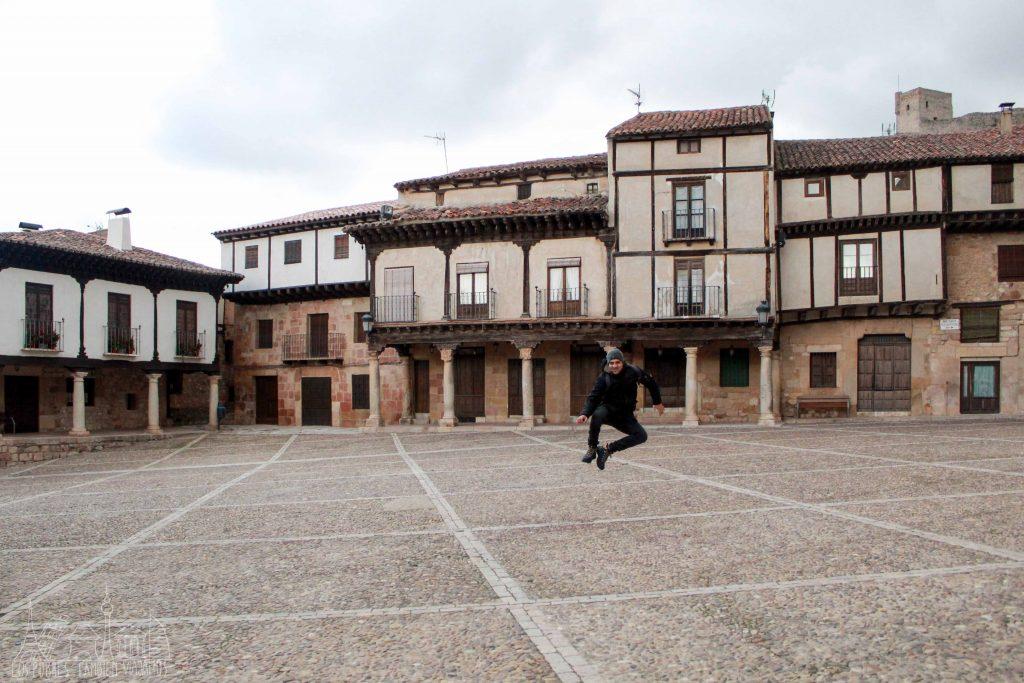 Casas medievales con maderas en la fachada, plaza con porches, firme de piedrecitas y JJ saltando en el medio.